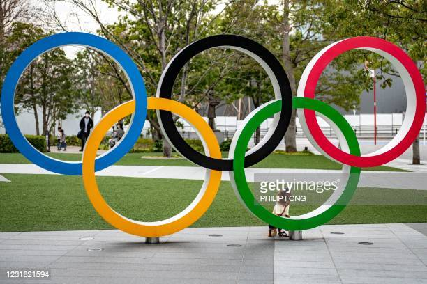 Dog stands next to the Olympic Rings outside the Japan Olympic Museum in Tokyo on March 20, 2021.