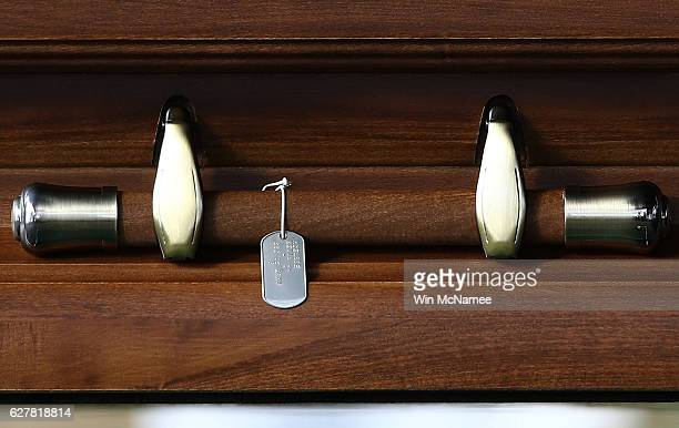 Dog tags hang from the casket of US Army Staff Sgt Kevin J McEnroe during the soldier's burial service at Arlington National Cemetery December 5 2016...