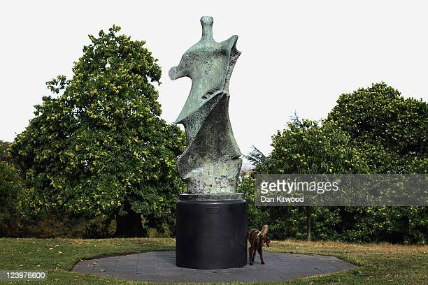 A dog urinates up a newly installed sculpture entitled 'Knife Edge' by Henry Moore in Greenwich Park on September 7 2011 in London England The...