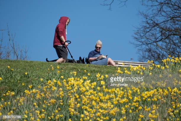 Dog walker passes a woman reading a book in the sun during the warm weather on March 29, 2021 in Southend, England. Today the government eased its...