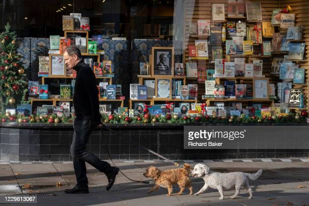 Dog walker passes Christmas books stock in the window of a closed Chelsea branch of Waterstones on the King's Road during the second Coronavirus...