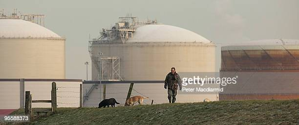 A dog walker passes near to the Liquefied Natural Gas importation terminal on January 5 2010 on the Isle of Grain England Cold weather has continued...