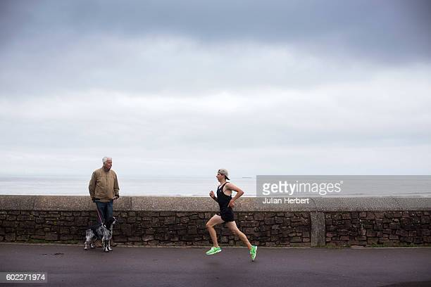 A dog walker watches a runner as tourists enjoy one of the last weekends of summer on September 10 2016 in Minehead England Situated on the south...