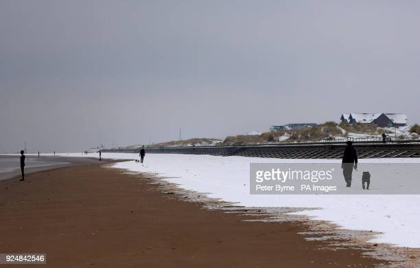 Dog walkers in the snow near to Another Place by Anthony Gormley on Crosby Beech near Liverpool following heavy overnight snowfall which has caused...