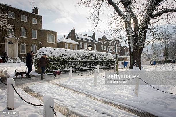 Dog walkers passby a Dulwich Village landscape during midwinter snow With sunshine now thawing the pavements after a week of freezing temperatures...