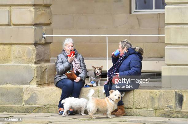 Dog walkers take a break while in Buxton Town Center on February 23, 2021 in Buxton, England.