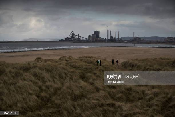 Dog walkers walk through sand dunes to Seal Sands Nature Reserve that look over the River Tees to the former SSI Steel works in Redcar on February 8...