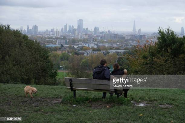 A dog walks near a bench where a couple are sat on Parliament Hill enjoying the backdrop view of the city skyline on a Sunday in Hampstead Heath park...