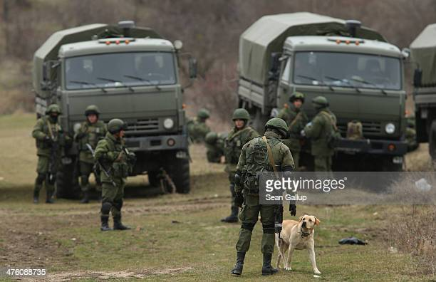Dog walks past Russian-speaking soldiers who were among several hundred that took up positions around a Ukrainian military base in Crimea on March 2,...