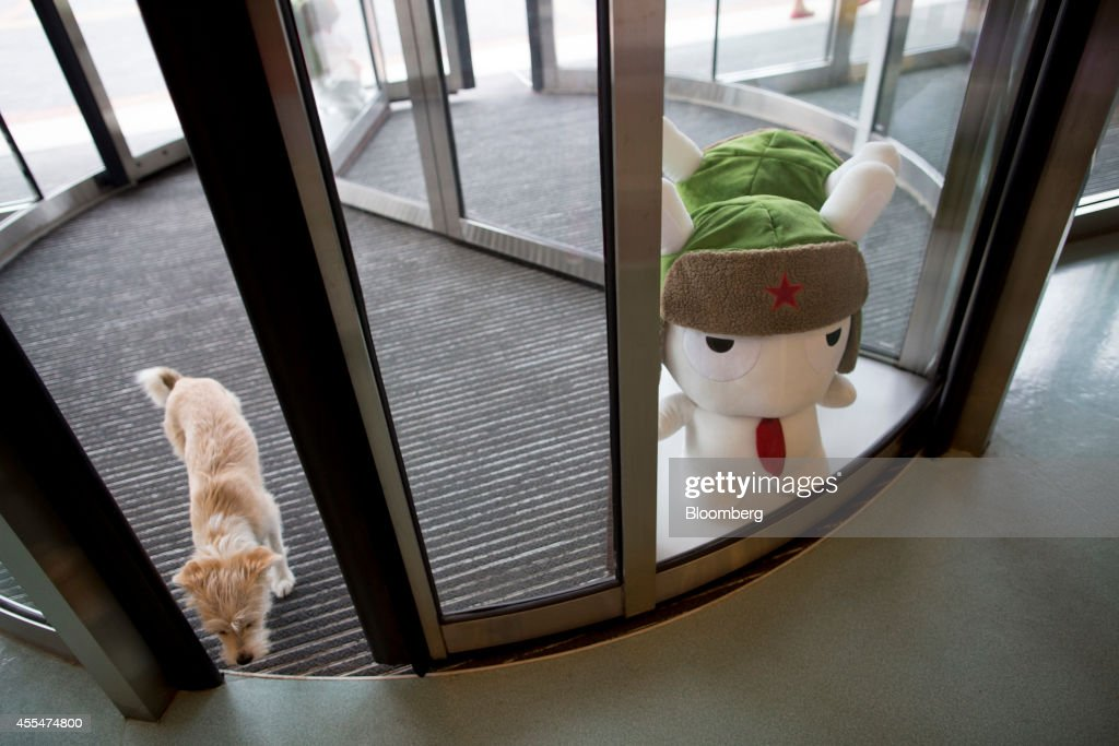 A dog walks through a revolving door as a plush toy of Mitu rabbit, the Xiaomi Corp. mascot, stands on display at a Xiaomi Corp. office in Beijing, China, on Friday, Sept. 12, 2014. Xiaomi Chief Executive Officer Lei Jun plans to boost global smartphone sales fivefold to 100 million units next year. Photographer: Brent Lewin/Bloomberg via Getty Images