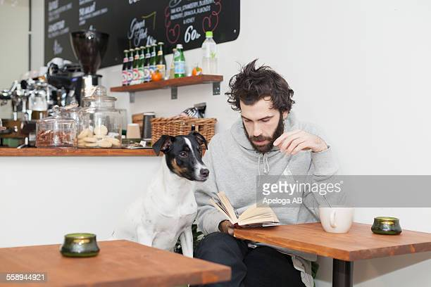 Dog with man reading book at cafeteria