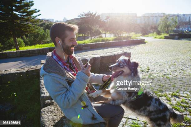 Dog with paws on owners lap in park