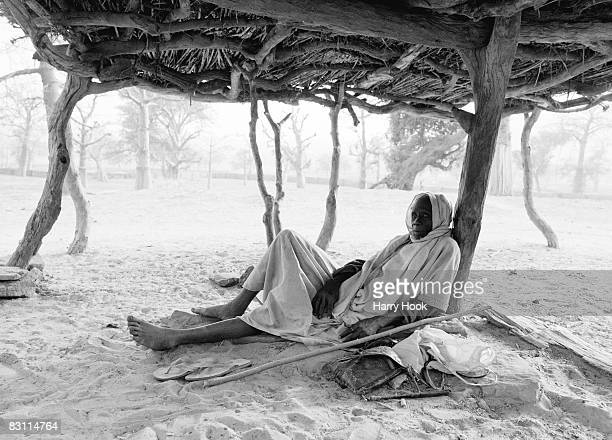 Dogon elder rests in the shade of a 'Casa palava' or 'to guna' Nombori Dogon Country Mali