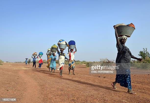 Dogon ethnic group women walk back to the village they left after Islamists arrived on February 1 2013 in Binta AFP PHOTO ERIC FEFERBERG