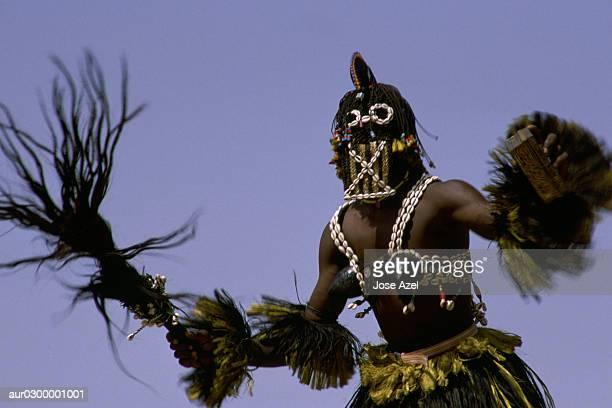 A Dogon man in his traditional costume as he dances during a celebration, Africa.
