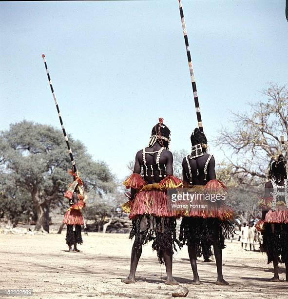 Dogon masqueraders perform in a ceremony known as a dama which draws the souls of honoured dead away from the village and brings prestige to their...