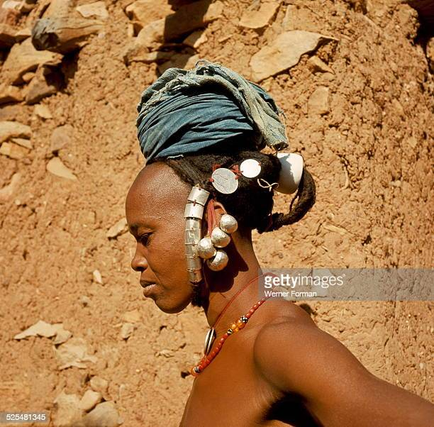 A Dogon woman her hair plaited through a shell ornament wearing a turban and jewellery Mali late 1950's early 1960's