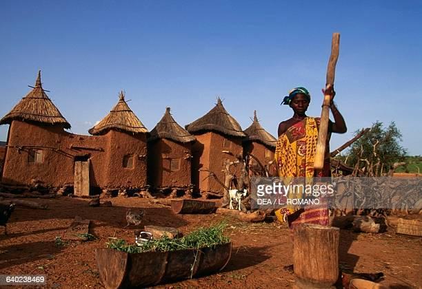 Dogon woman pounding millet village Kundu Mali