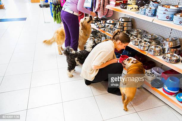 Dogs and his owners in pet store buying new bowl