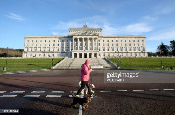 A dogwalker passes the Parliament Buildings on the Stormont Estate the seat of the Northern Ireland assembly in Belfast on January 24 2018 Northern...