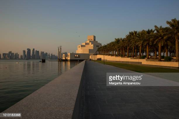 Doha Corniche separating the modern cityscape from the palm trees and the museum
