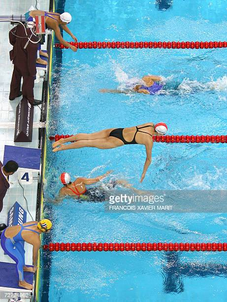 A member of the Chinese team dives into the water as members of Thailand and Japan wait for the exchange in the women's 4x200m freestyle relay...