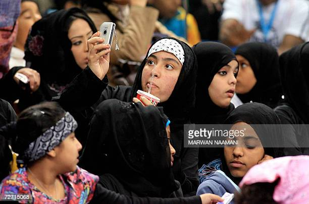Veiled Qatari youth takes pictures using her mobile phone as she follows with her colleagues the competition of women Artistic Gymnastics Individual...