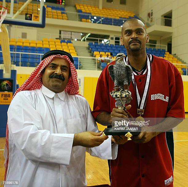 Angolan Capitan Ricardino receives the trophy from Sheikh Saud bin Ali al-Thani, the vice president of Qatar's Olympic Committee, after the final...
