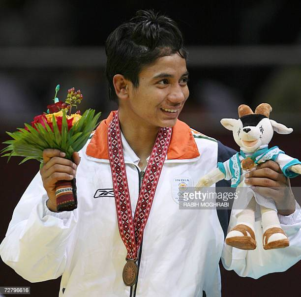 Bronze medalist Alka Tomar of India poses on the podium of the women's freestyle wrestling 55kg competition at the 15th Asian Games in Doha 11...