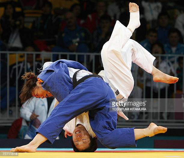 Chinese judoka Xu Yuhua throws South Korea's Kong JaYoung to win by ippon during their 15th Asian Games women's judo under 63kg final at the Qatar...
