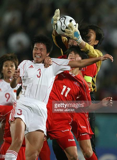 Chinese soccer player Li Jie vies with Ri Un Gyong and Jon Myong Hui of North Korea during the women's semifinal football match at the 15th Asian...