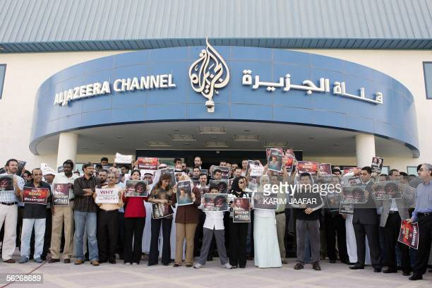 Employees of Qatari satellite channel alJazeera display slogans as they protest in front of their headquarters in Doha 24 November 2005 Journalists...