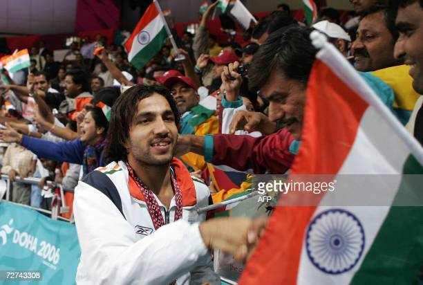 Indian kabaddi player Manpreet Singh is greeted by fans after defeating Pakistan and winning the gold in the men's kabaddi final match at the 15th...