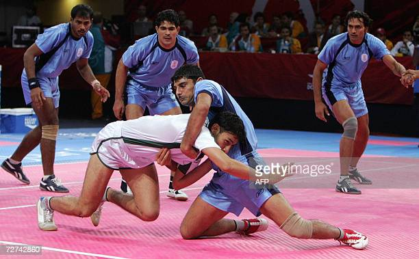 Indian Sukhvir Singh holds Pakistan's Wajid Ali during the men's kabaddi gold final match at the 15th Asian Games in Doha 06 December 2006 AFP PHOTO/...