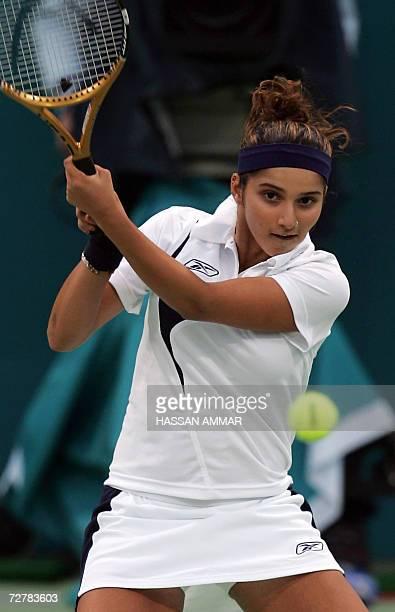 India's tennis player Sania Mirza returns a shot to Murad Inoyatov and Dilyara Saidhodjaeva of Uzbekistan during their mixed doubles round of 16...