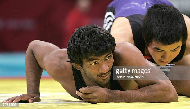 India's Yogeshwar Dutt battles with Bauryrzhan Orazgaliyev of Kazakhstan in the men's freestyle 60kg bronze medal wrestling match at the Aspire Hall...