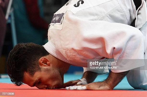Iranian judoka Arash Miresmaeili kisses the tatamimat after beating Turkmenistan's Guvanch Nurmuhammedov in the Asian Games judo men's under 66kg...