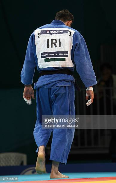 Iranian judoka Arash Miresmaeili walks off the mat after loosing to Mongolia's Tsagaanbaatar Haskhbaatar in their Asian Games judo men's under 66kg...