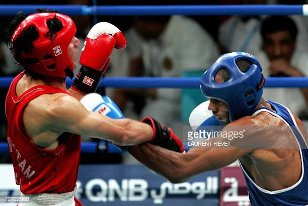 Iraqi Jabar Zuhir throws a punch at Afghan boxer Mohammad Naim Amini in their super lightwight 64kg preliminary bout during the 15th Asian Games in...