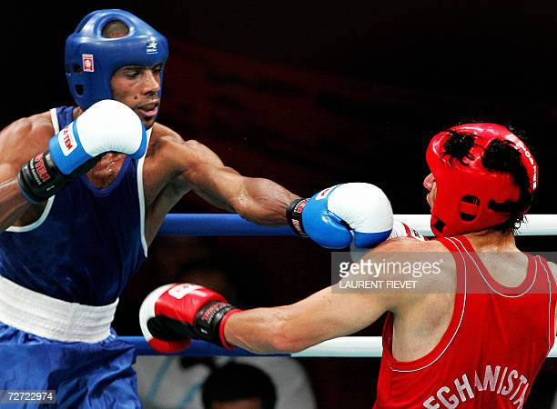 Iraqi Jabar Zuhir throws a punch to Afghan boxer Mohammad Naim Amini in their super lightwight 64kg preliminary bout during the 15th Asian Games in...