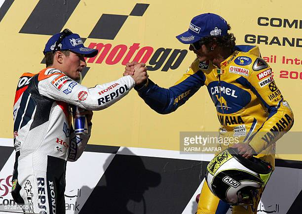 Italian rider and world champion Valentino Rossi celebrates after winning the Qatar MotoGP World Championship with the runner up Nicky Hayden of the...