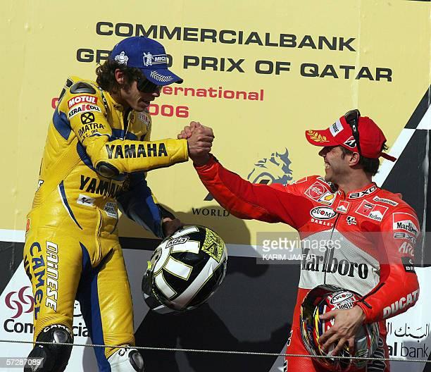 Italian rider and world champion Valentino Rossi celebrates after winning the Qatar MotoGP World Championship with third place winner Loris Capirossi...