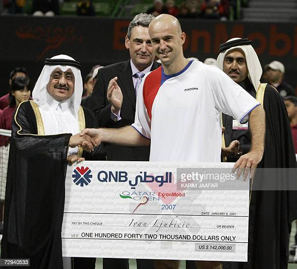 Ivan Ljubicic of Croatia receives a cheque from Mohammed alShamlan head of Qatar National Bank after winning the onemillion dollar Qatar Open final...