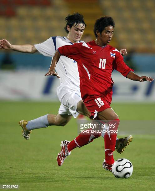 Kyrgyzstan's Evgeny Malinin tries to intercept Thailand's Tana Chanabut during their round two Group C match at the 15th Asian Games in Doha 02...