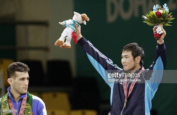 Mongolia's Tsagaanbaatar Haskhbaatar raises his arms in jubilation on a podium as silver medalist AS Arash Miresmaeili of Iran looks at him after...
