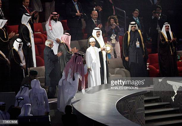 Qatar Emir Sheikh Hamad bin Khalifa AlThani stands with a performer in the VIP stand at the 15th Asian Games14 December 2006 in Doha AFP PHOTO/KHALED...