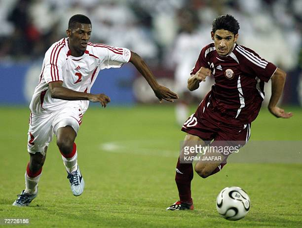 Qatar national team soccer player Hussein Yasser vies with Bader alJuraishi of the United Arab Emirates during the men's round 2 group A football...