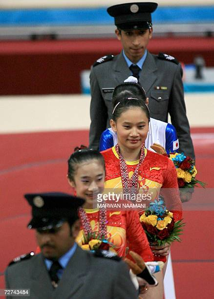 Qatari security officials escort gold medalist Chinese gymnast Zhang Nan fellow Chinese silver medalist Han Bing and bronze medalist Japanese gymnast...