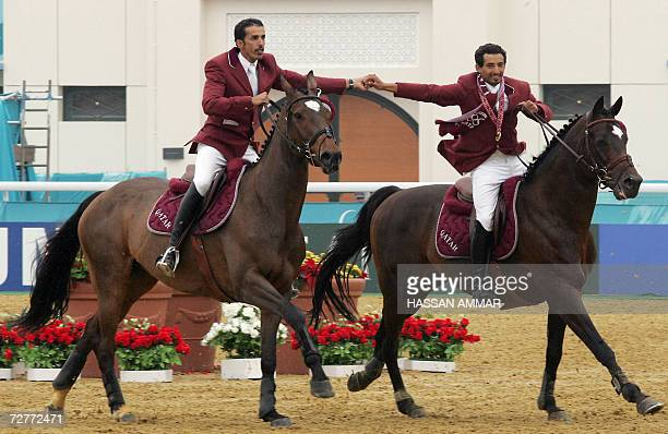 Qatar's Mohammed Awad alQahtani and Alat Faraj alMarri celebrate after winning the the gold medal at the Equestrian Team Jumping competition during...