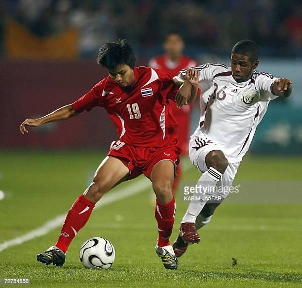 Qatar's soccer player Khalfan Ibrahim vies with Hadtaporn Suwan of Thailand during their quarterfinal football match at the AlGharrafa Sports Club...